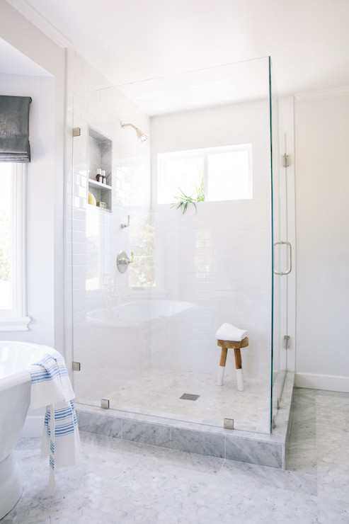 master bathroom features a corner seamless glass shower filled with white subway tiles framing window and tiled shower niche under shower head as well as a