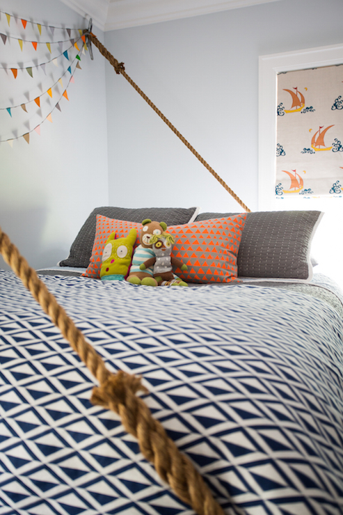 adorable boyu0027s bedroom features light blue walls alongside a sash window dressed in a nautical roman shade in katie ridder beetlecat fabric beside hanging