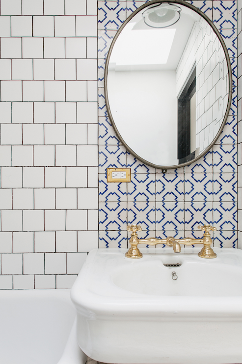 amazing bathroom features a bathtub shower combo next to white porcelain sink fitted with a polished gold bridge faucet under a white and blue geometric