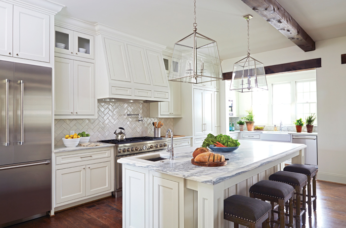 Gorgeous Kitchen Features White Shaker Cabinets Paired With Marble  Countertops And A White Herringbone Pattern Backsplash.