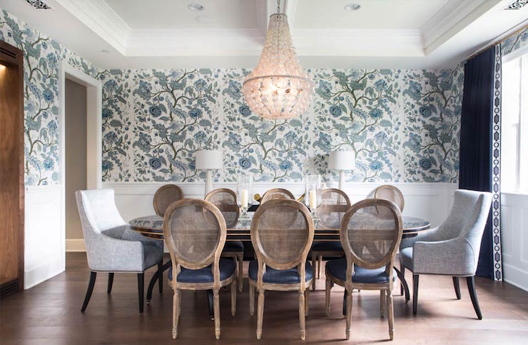beautiful dining room features an oly studio ariel chandelier an oval dining table lined with oval back cane dining chairs with dark blue