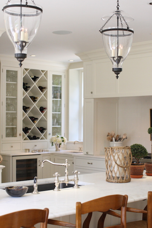 Beautiful Kitchen Features A Pair Of Glass And Iron Lanterns Illuminating A  Long Island Topped With Honed White Marble Framing A Stainless Steel Sink  And ...