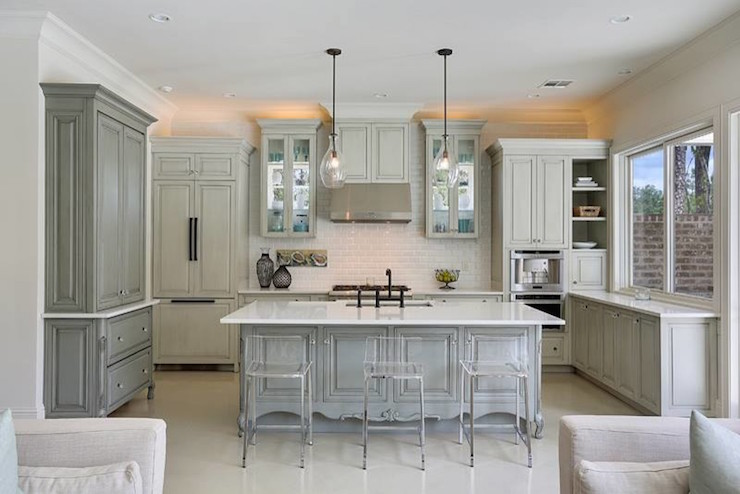 gray kitchen features gray wash cabinets paired with white marble countertops and a white beveled subway tiled backsplash