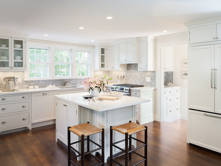with white countertops and a honed bardiglio marble tile backsplash