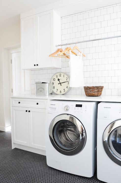 Vintage laundry room features a tension rod between white cabinets adorned  with oil-rubbed bronze knobs suspended over a white front load washer and  dryer ...