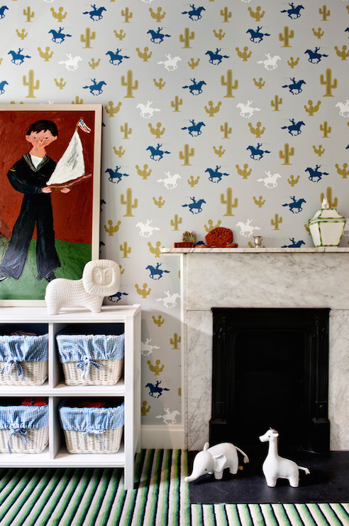 Fun boy's room features walls clad in Cactus Cowboy Wallpaper lined with an  open bookcase filled light woven baskets accented with blue gingham fabric  ...