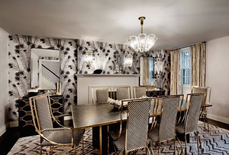 Stunning Dining Room Boasts A Glass Chandelier Illuminating A Black Marble Dining  Table With Gold Trim Lined With Black And White Stripe Dining Chairs Atop  ...