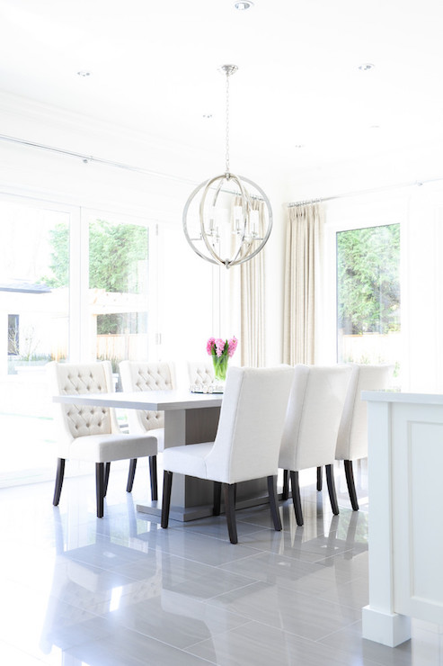 Light And Bright Dining Room Features A Gray Pedestal Table Lined With White Wingback Chairs Illuminated By Polished Nickel Sphere Pendant
