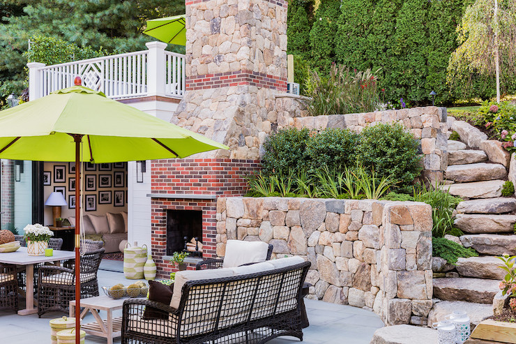 Amazing patio features a stone and brick outdoor fireplace lined with a zinc mantle placed in front of an outdoor living and dining space boasting an outdoor dining table lined with brown wicker dining chairs beside a brown outdoor wicker sofa paired with an outdoor coffee table covered by a lime green patio umbrella.