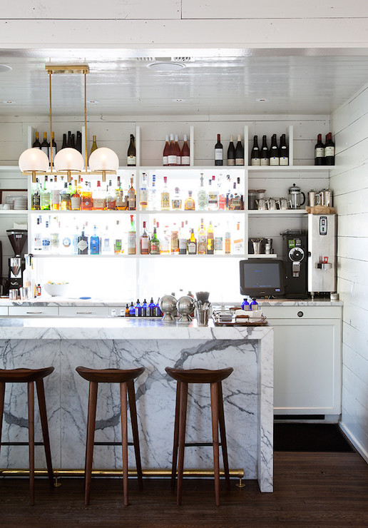 Attractive Amazing Wet Bar Features 3 Light Brass Linear Chandelier Illuminating A  Marble Kitchen Island Lined With DWR Tractor Stools Alongside Stacked  Shelves Placed ...