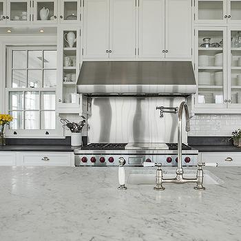 beautiful kitchen features a center island topped with white marble