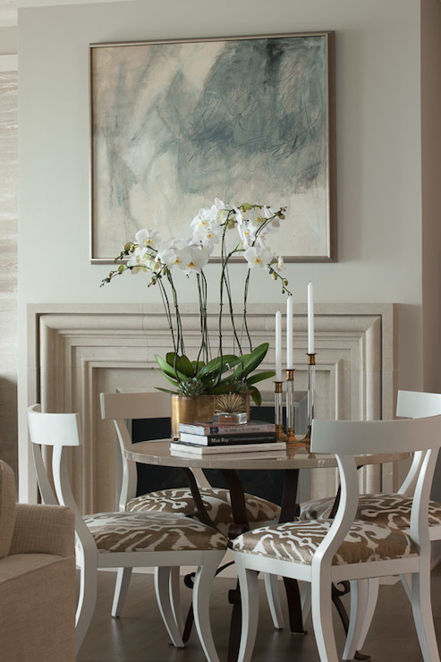 Elegant Dining Room Boasts A Round Table Lined With White Klismos Chairs Accented Taupe Ikat Seat Cushions Placed In Front Of Limestone