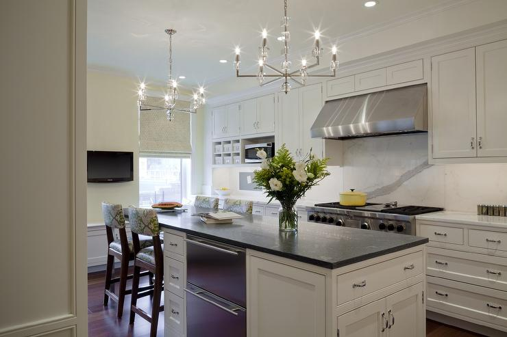 Illuminating A White Kitchen Island Fitted With Stacked Pull Out Dishwashers And Topped Contrasting Black Countertops Next To Drop Down Dining