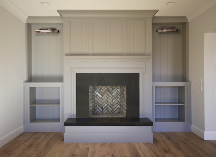 Living room fireplace boasts a gray fireplace wall fitted with a gray fireplace mantle and black fireplace surround hearth flanked by gray built-in cabinets accented lined with gray beadboard illuminated by picture lights.
