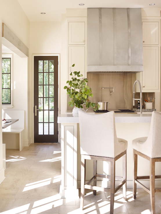 Cottage Kitchen Features Ivory Cabinets Paired With Thick White Marble  Countertops And A Stainless Steel Backsplash Alongside A Stainless Steel  Barrel Hood ...