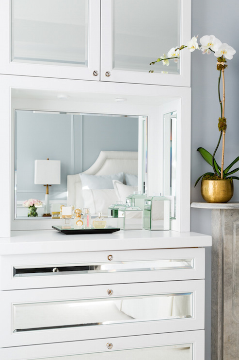 Charming White And Blue Bedroom Boasts A Marble Fireplace Adorned With A Gold Pot  Filled With A White Orchid Beside Built In Mirrored Cabinets Stacked Over A  Shelf ...