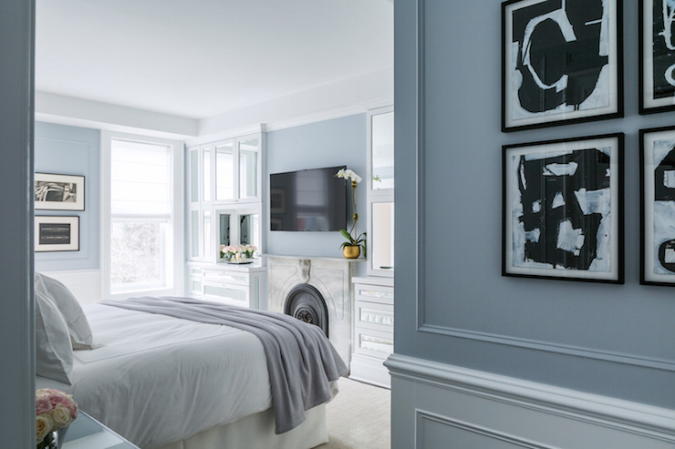 White and blue bedroom boasts a flatscreen TV over a marble fireplace  adorned with a gold pot filled with a white orchid flanked by built in  mirrored. Bedroom Built In Cabinets Design Ideas