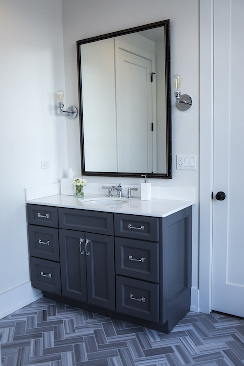 fantastic bathroom features a black rivet vanity mirror illuminated by bare bulb sconces over a dark gray washstand topped with white quartz countertop atop