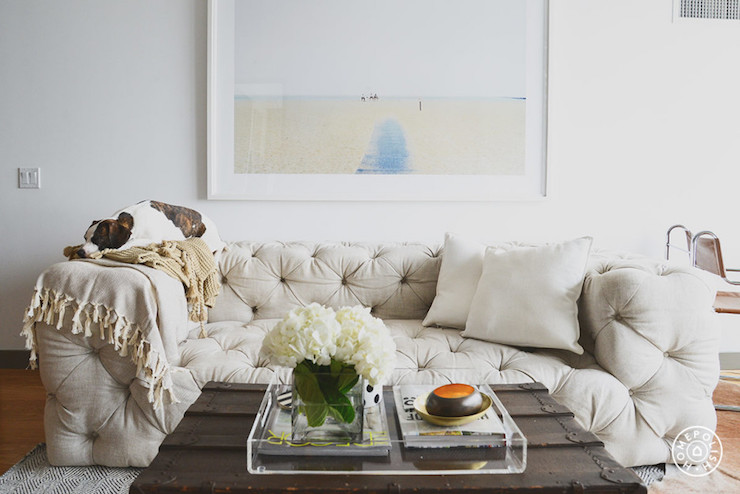 Amazing Living Room Features A Framed Beach Photograph Over Low Tufted Sofa Restoration Hardware Soho Upholstered Draped In White Shams And Gray