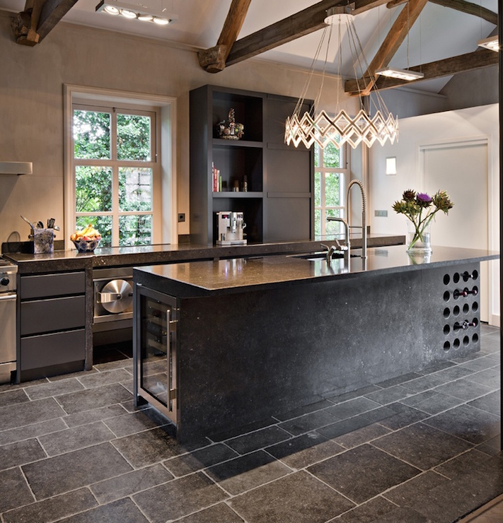 ... with rustic wood beams and a round accordion chandelier illuminating a black kitchen island fitted with built-in wine rack and wine cooler topped with ...
