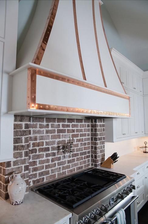 white and black kitchen with white exposed brick backsplash