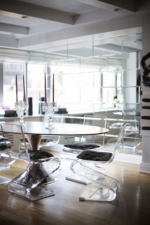 Contemporary dining room features an oval dining table lined with Plexi-Craft Acrylic Z Chairs accented with black and white cushions placed in front of a ... & Acrylic Dining Chairs Design Ideas