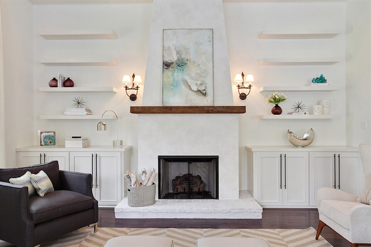 Simply stunning living room features a white plastered fireplace accented with a chunky wood mantle lined with a gorgeous aqua and black abstract piece illuminated by iron sconces.