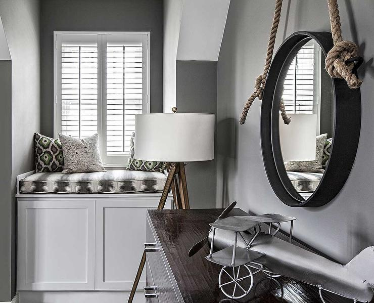 Gray kid s bedroom features walls painted charcoal gray lined with a rope  hung captain s mirror over a dark stained dresser topped with a vintage  model. Mirror Over Kids Dresser Design Ideas