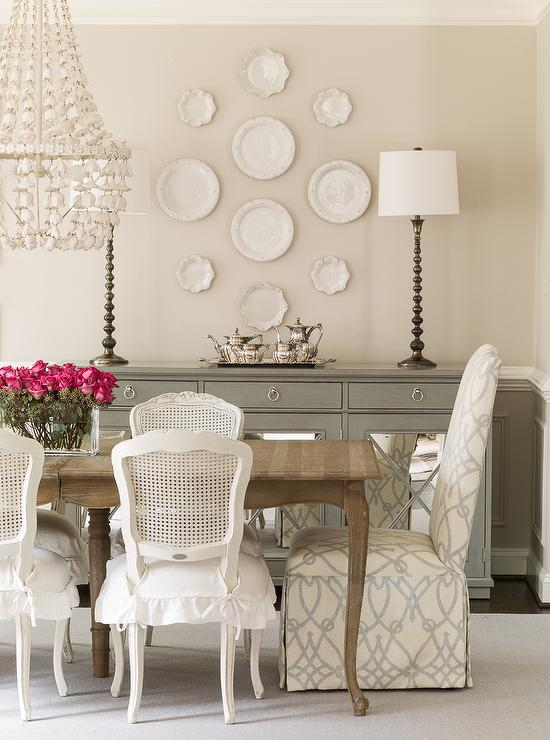 Stunning Dining Room Features A Carved Wood Table Lined With White Cane Back Chairs Skirted Seat Cushions As Well Slipper Captain