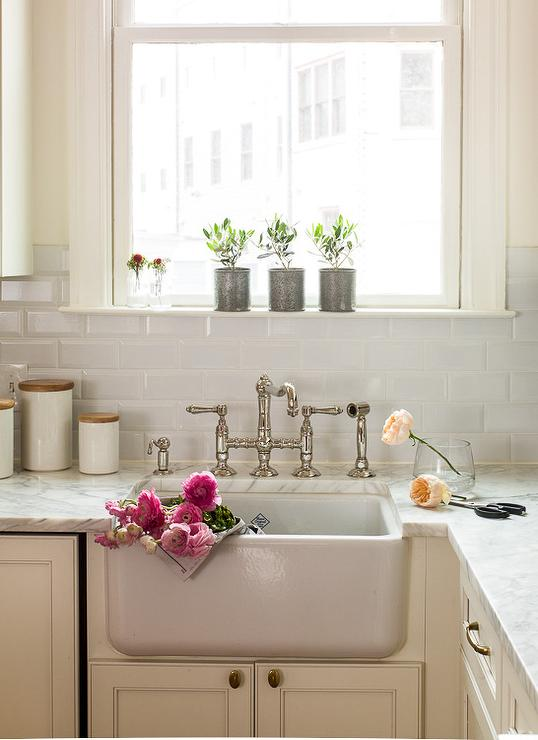 Kitchen Backsplash By Window ivory kitchen cabinets with beveled subway tile backsplash