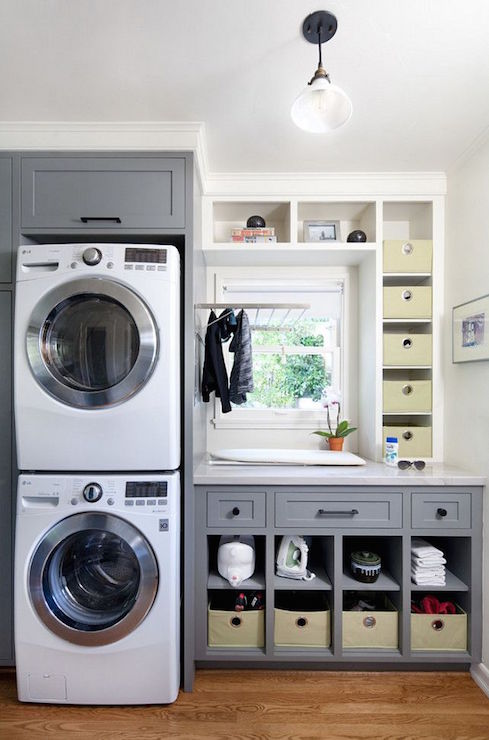 Gray Laundry Room Features Stacked Washer And Dryer Enclosed In Gray  Cabinets Situated Next To Gray Cabinets And Cubby Holes Topped With White  Marble ...