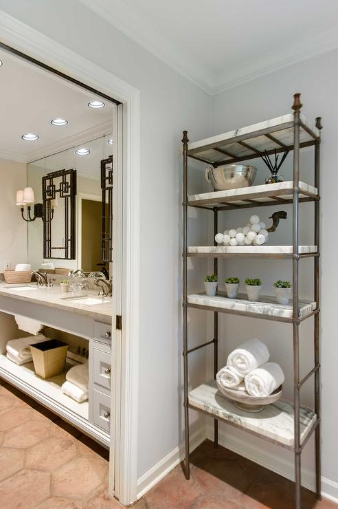 hallway features a metal and marble etagere atop terracotta hexagon tiled floor next to pocket door opening to master bathroom