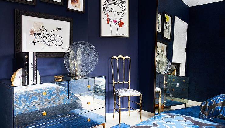 Chic blue bedroom features walls painted royal blue lined with a collection  of abstract sketches over a 4 drawer mirrored dresser adorned with gold  knobs. Blue And Gold Bedrooms Design Ideas
