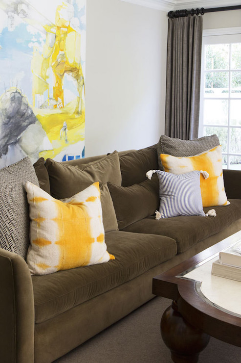 Molly Sims   Yellow And Brown Living Room Features A Brown Velvet Sofa  Accented With Yellow Pillows Placed Under A Blue And Yellow Abstract Art  Piece.