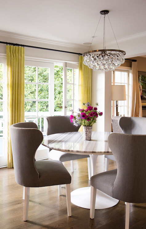 molly sims fabulous dining room features an ochre arctic pear chandelier hanging over a saarinen dining table lined with gray wingback dining chairs