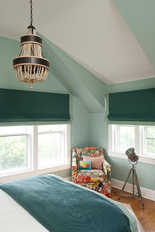 Green On Green Bedroom Features Walls Painted Green Alongside A A Cream And Black Beaded Chandelier Hanging Over A Bed Dressed In Green And Teal Bedding