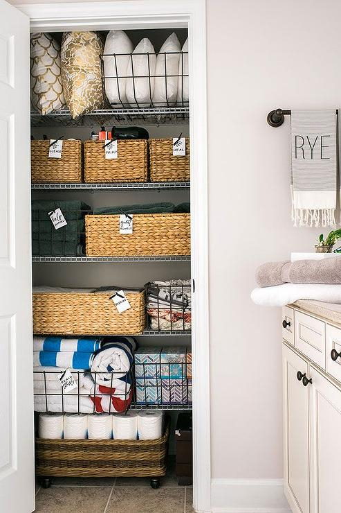 well organized bathroom linen closet features woven baskets and wire
