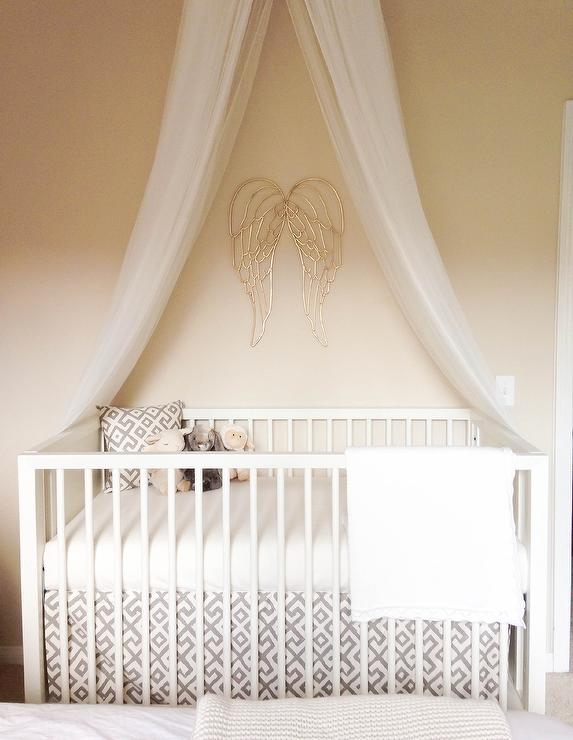 Sweet nursery boasts a a tulle crib canopy situated over angel wings painted gold from Hobby Lobby and a DwellStudio Mid-Century Crib French White dressed ... & Canopy Crib Design Ideas