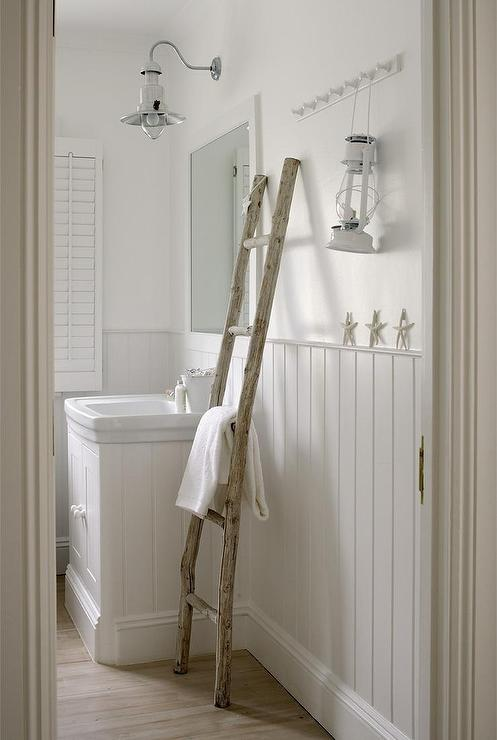 White Cottage Bathroom Features Upper Walls Painted White And Lower Walls Clad In Beadboard Trim Lined With A Beadboard Clad Washstand Topped With A White