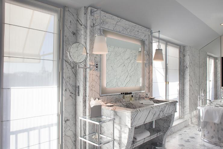 Chic Hotel Bathroom Features Marble Cad Floors And Walls Lined With A Marble  Washstand Fitted With A Marble Dual Sink Under An Inset Lit Vanity Mirror  ...