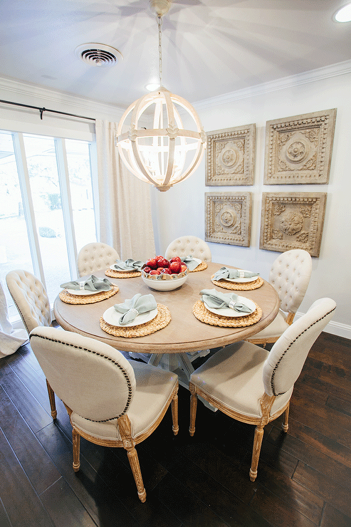 Chic French Dining Room Features A Wood Sphere Chandelier Illuminating Round Table Lined With Cream Tufted Chairs