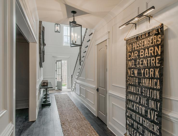 Beautiful Hall To Foyer Features Full Wall Wainscoting Lined With A Vintage Subway Sign Illuminated By Picture Light Next Gray Door Situated Under The