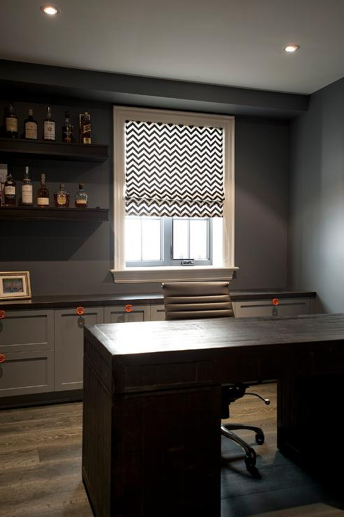 chic home office features charcoal gray wall lined with chunky floating bar shelves filled with libations next to window dressed in a black and white chic home office features