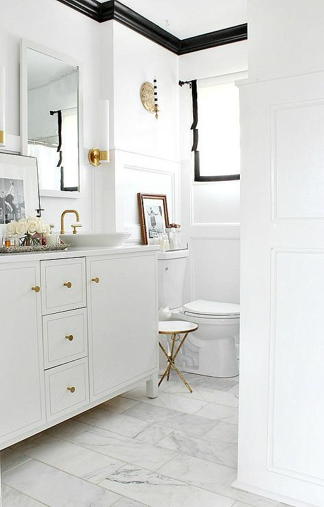 black and white bathroom features white walls finished with black crown moldings lined with a white vanity by kohler adorned with gold knobs topped with his