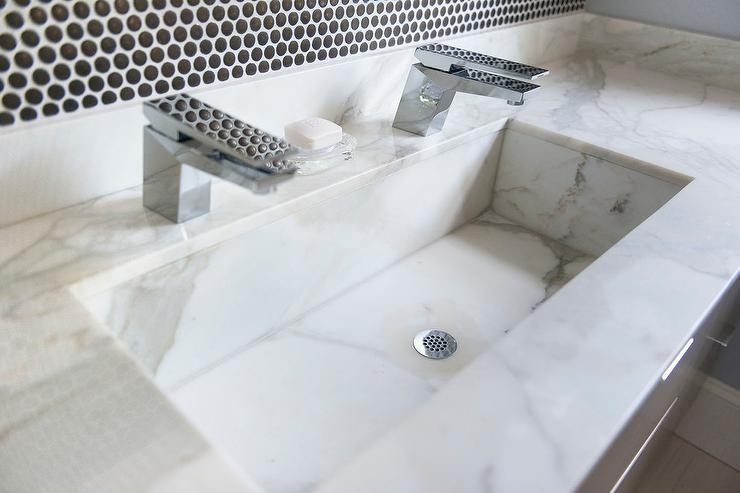 Contemporary bathroom features a taupe veneer floating vanity topped with  white marble fitted with a white marble trough sink paired with his and her  ...