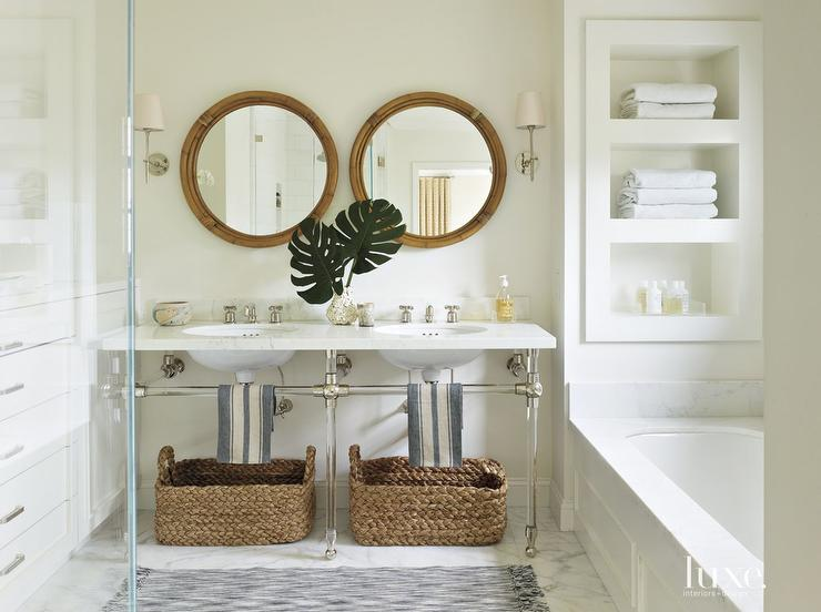 chic coastal bathroom features a pair of round bamboo vanity mirrors illuminated by thomas obrien bryant sconces situated over a nickel and glass dual - Coastal Bathroom