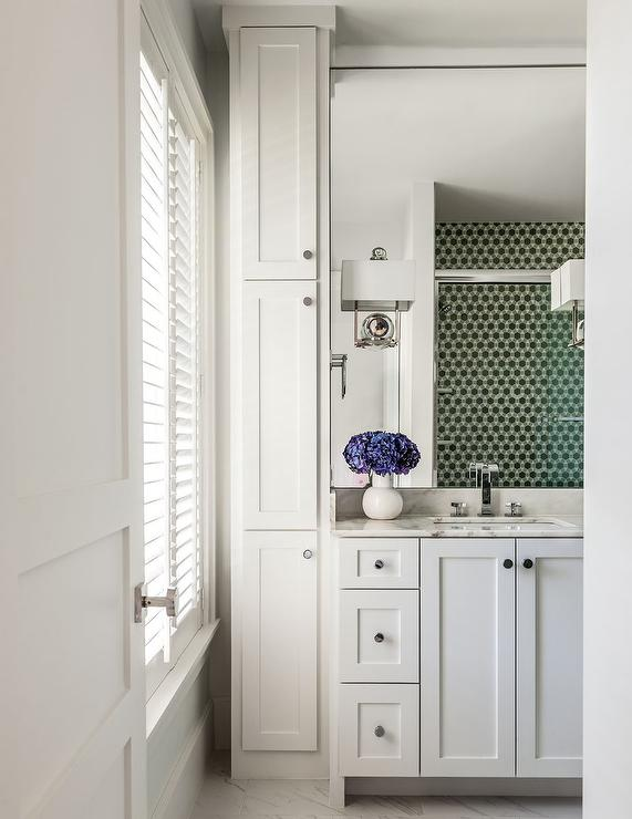 wonderful bathroom features a white shaker vanity adorned with nickel knobs topped with gray and white marble under a full height mirror illuminated by