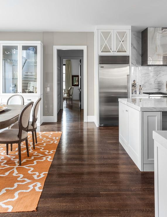 Open Plan Kitchen Features A Dining Room Boasting Gray Weathered Oval Table Lined With French Round Back Chairs Atop An Orange Rug