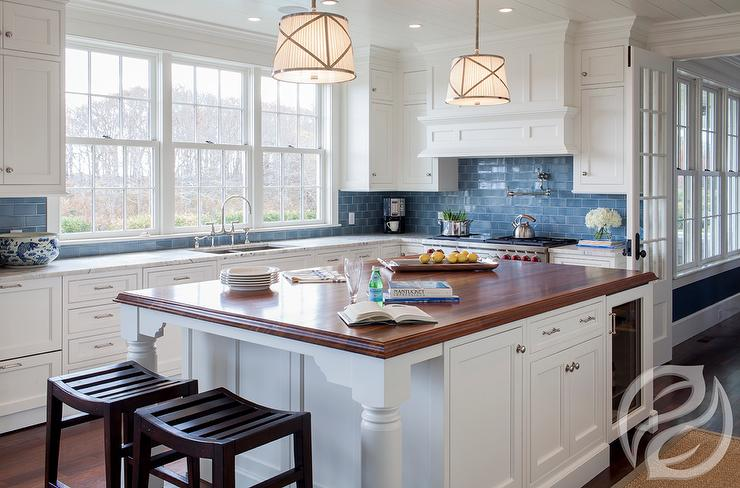 White And Blue Kitchen Features Cabinets Paired With Marble Countertops A Subway Tiled Backsplash