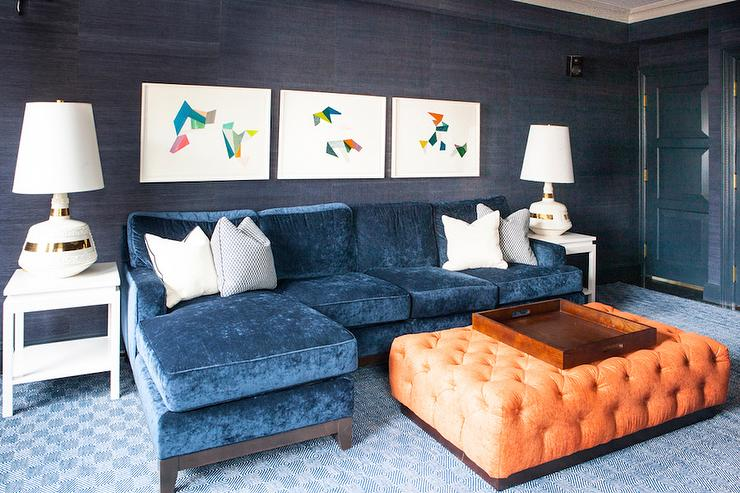 a peacock blue paneled door opens to an orange and blue family room features walls clad in dark blue grasscloth lined with three abstract art pieces over a